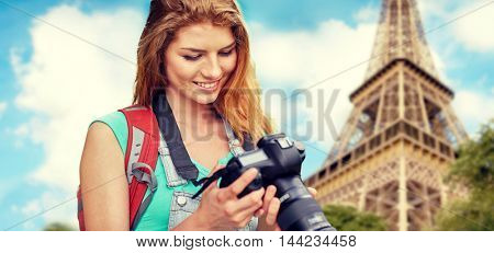travel, tourism and people concept - happy young woman with backpack and camera photographing over eiffel tower background