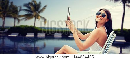 summer vacation, tourism, travel, holidays and people concept - smiling young woman with tablet pc sunbathing in lounge or folding chair over resort beach with palms and swimming pool background