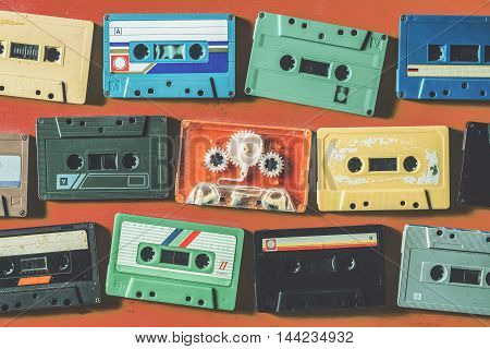 Old cassette tapes on orange wooden table top view