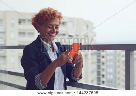 Mature woman using a smartphone on the balcony