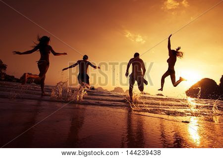 Group of happy young people is running on background of sunset beach and sea. Krabi province, Thailand