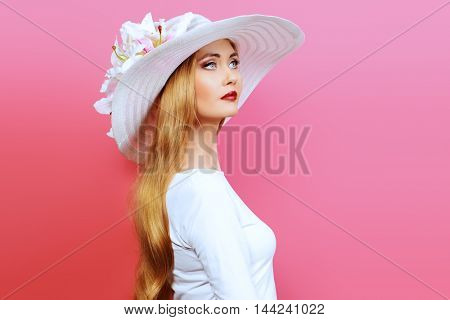 Portrait of a beautiful woman in elegant hat over pink background. Beauty, fashion. Summer vacation.