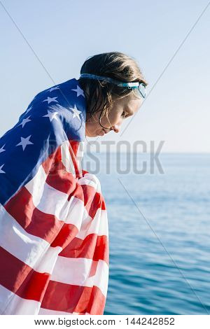 side view of young wet-haired woman looking down in american flag and swimming goggles in sunlight.Seascape on background.