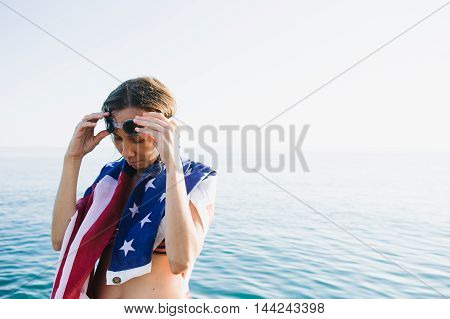 Portrait of young woman in goggles wearing american flag on shoulders against of sea blending with sky.Copy space.