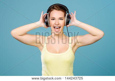Modern girl enjoys listening to music in headphones. Positive emotions, leisure.