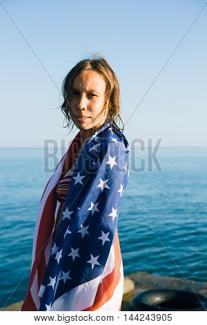 Side view of young woman wrapped in american flag on pier looking at camera against of seascape