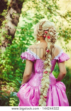 Beautiful girl with long hair braided in a braid in a beautiful hairstyle in a corset and a magnificent pink dress standing with her back in the woods.