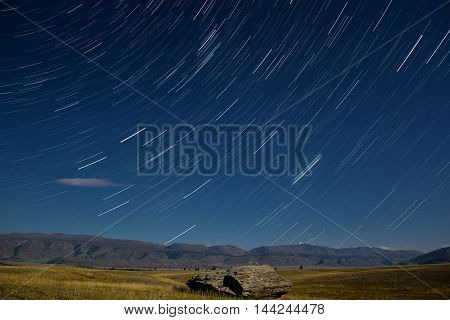 Beautiful night landscape with cloud and traces of the stars in the night sky against a background of mountains shot with a long exposure
