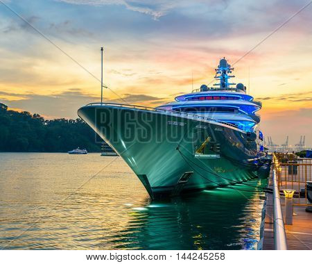 Docked green yacht at sunset in Singapore