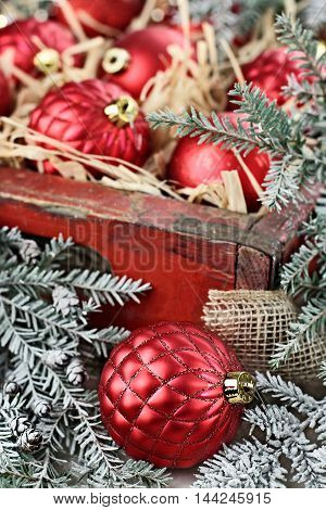 Glass Christmas ornaments packed in an old antique wooden box with snow covered pine boughs surrounding them. Extreme shallow depth of field with selective focus on bauble in front.