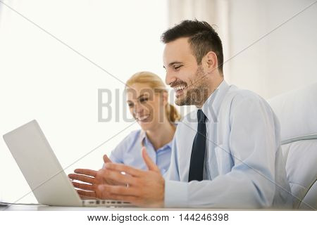Image of two successful business people working at meeting in office.Businessman using his laptop.He is wearing a blue shirt and a black tie.