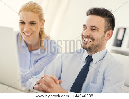 Business people working at meeting in office.Businessman using his laptop.He is wearing a blue shirt and a black tie.