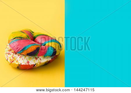Colorful bagel on yellow and blue background