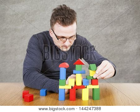 Man builds the house of children's toy blocks