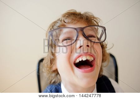 Funny little schoolboy. Kinky boy in huge glasses carefree laughs. He has a good mood. This is a primary school pupil.