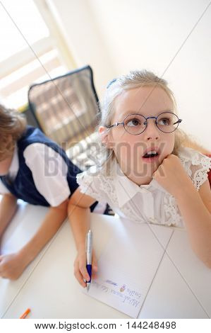 Small schoolgirl of an elementary school sits at a school desk in thoughtfulness. Girl rested her head on his hand and looking dreamily somewhere. Nearby sits her classmate.