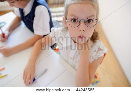 Two young student of an elementary school sitting at a desk. On the desk there are textbooks and school supplies. The boy is writing something. Schoolgirl in glasses looking into camera with surprise.