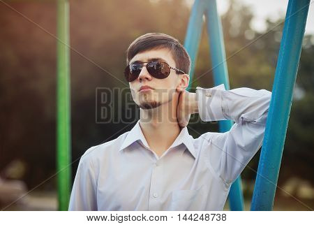 Handsome stylish young man with beard in sunglasses and white shirt with long sleeves relaxing outdoors, enjoying warm sunny day