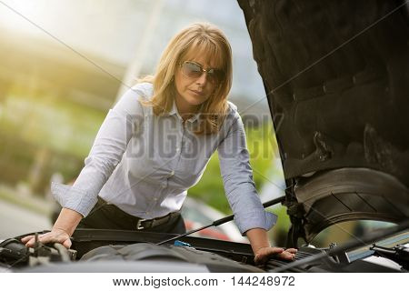 Beautiful mature woman with car trouble in the middle of the streetafter car breakdown.