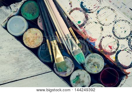 Artist paint brushes on background of gouache paint jars. Brush, paint, artistic. Tools for creative work. Watercolor paintbox. Back to school. Paintings Art Concept. Top view.