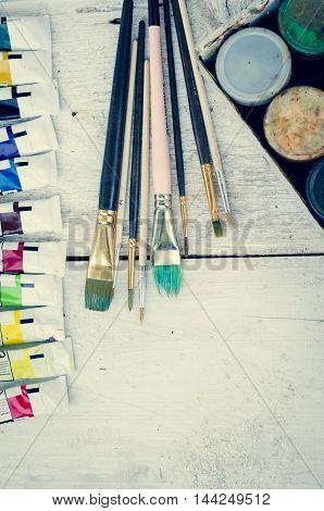 Artist paint brushes, oil paint tubes and gouache paint jars on white wooden background. Brush, paint, artistic. Tools for creative work. Back to school. Paintings Art Concept. Top view. Copy space.
