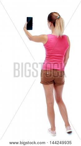 back view of standing young beautiful  woman  using a mobile phone. girl  watching. Rear view people collection.  backside view of person.  Isolated over white background. Sport blond in brown shorts