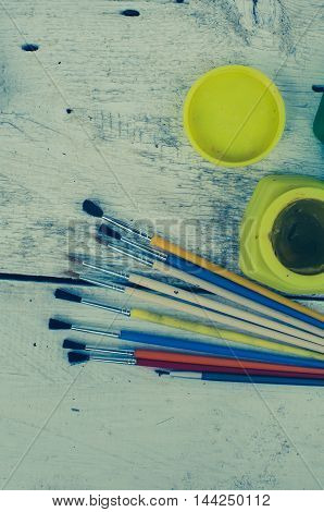 Tools for creative work on a white wooden background. Watercolor paintbox. Color paints with paint brushes. Back to school. Kids painting concept. Children art. Top view. Copy space.