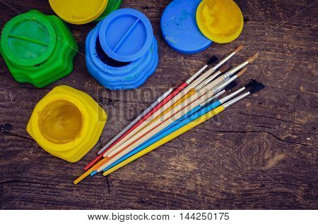 Color paints with paint brushes. Tools for creative work on a wooden background. Watercolor paintbox. Back to school. Kids painting concept. Children art. Top view. Copy space.