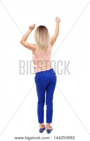 back view of dancing young beautiful  woman. girl  watching. Rear view people collection.  backside view of person.  Isolated over white background.  Blonde in blue pants waving his hands to the music