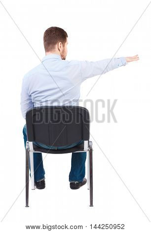 back view of young business man sitting on chair and pointing. Rear view people collection. Bearded businessman in white shirt sitting on the chair arm and points to the side.