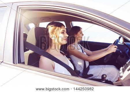 Young and beautiful girls driving car. Friends or sisters on a vehicle journey. Vacation and traveling concept.