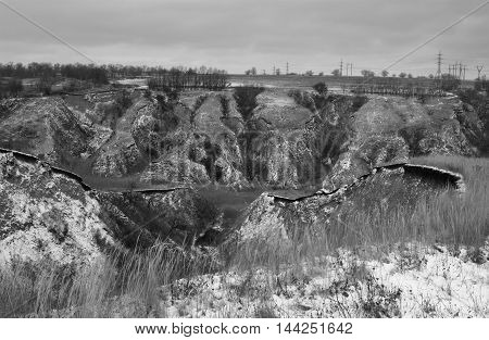 Gloomy winter landscape with soil erosion in black and white version.