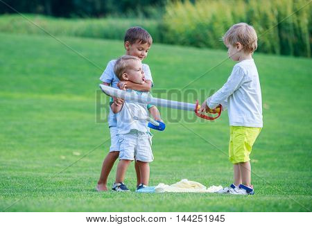 Two older boys fighting with toddler boy and threatening him with toy sword