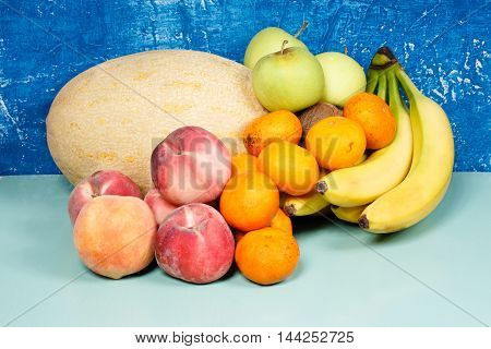 Harvest. Still life with melon peaches apples bananas tangerines and kiwis