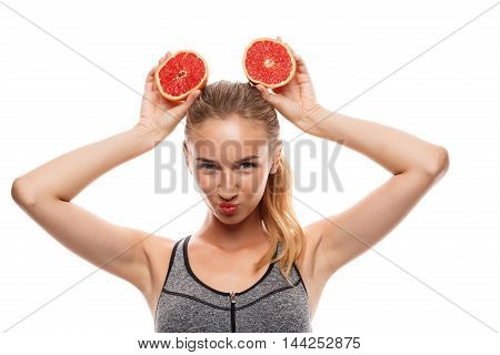 Young beautiful sportive girl posing, holding grapefruit over white background. Copy space.
