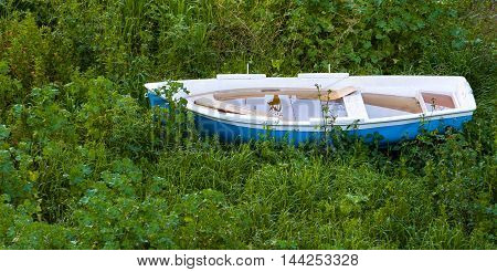 old boat old boat in a grass old boat abandoned on the field Old destroyed wooden boats on the ground