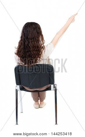 back view of young beautiful  woman sitting on chair and pointing.  girl  watching. Rear view people collection. Long-haired curly girl sitting on a chair and shows up finger.
