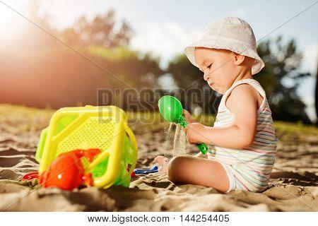Baby boy playing with beach toyshaving fun on the beach.