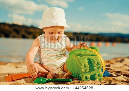 Baby boy playing with toys on the beach
