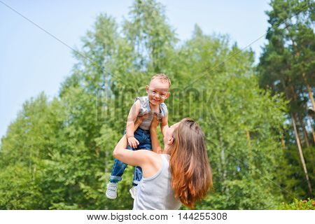 Happy family. Young mother throws up baby in the sky, on sunny day. Positive human emotions, feelings, joy.