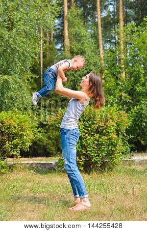 Happy family. Young mother throws up baby on sunny day. Positive human emotions, feelings, joy.