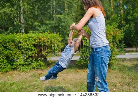 Happy family having fun outdoors. Mother holding son and spin like carousel. positive emotions.