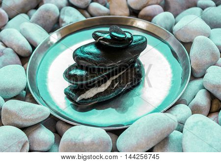 Spa still life with stone pyramid reflecting in water. The perfect balance of black stones.