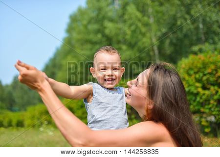 Happy family having fun outdoors. Mother and playing in park, positive emotions.