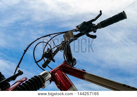 Red Bicycle Handle Bars Against A Blue Sky