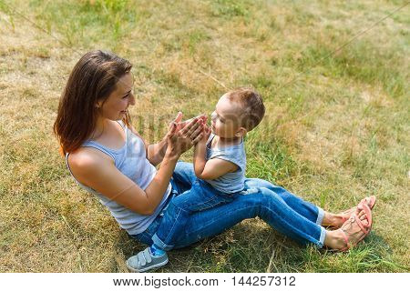 Young mother sitting face to face to her cute toddler son playing clapping hands in park, lifestyle fun concept.