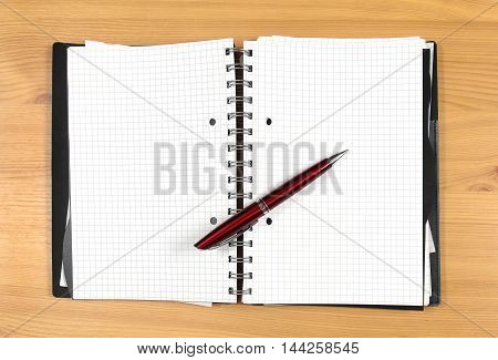 Open notebook with empty pages and pen on top