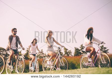 Enjoying nice summer day together. Group of young people riding bicycles and looking happy