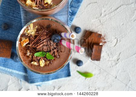 chocolate smoothie with banana blueberries and almonds on a concrete background