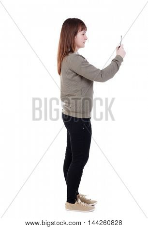 back view of standing young beautiful woman using a mobile phone. girl watching. Isolated over white background. she is cancer and makes selfie phone.